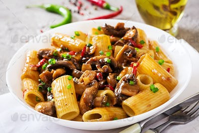 Vegetarian pasta  rigatoni with mushrooms and chilli peppers in white bowl on grey table.