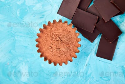 Cocoa beans background on blue table. Dark chocolate pieces