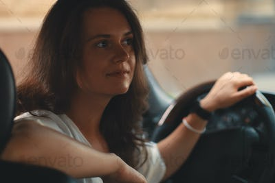 Close-up portrait of woman holding hand on steering wheel