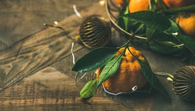 Fresh tangerines with leaves and decoration toys on wooden background