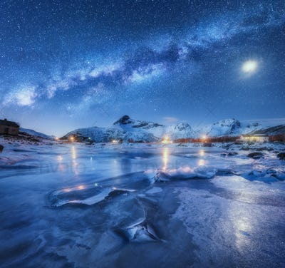 Milky Way above frozen sea coast, snow covered mountains