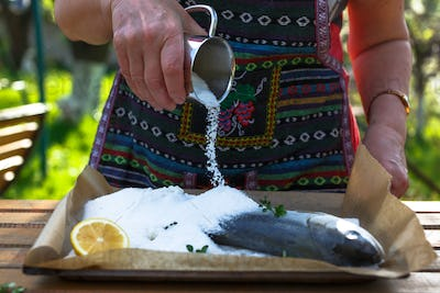 A woman cook a fish in a salt crust.