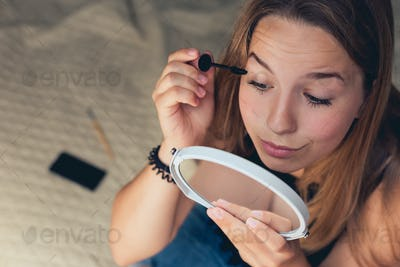 Young beautiful woman doing make-up in front of mirror