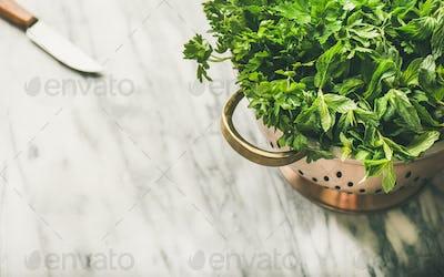 Bunch of fresh garden herbs in brass colander, marble background