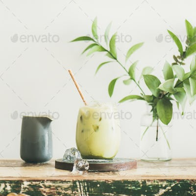 Iced matcha latte with milk pouring from pitcher, square crop