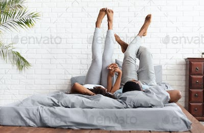 Happy couple lying on bed at home raising legs up