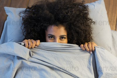Beautiful black woman hiding behind blanket and smiling