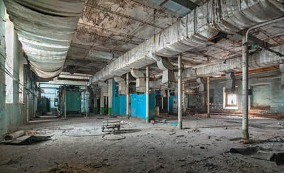 Destroyed production room of an old abandoned textile factory with remains of broken equipment