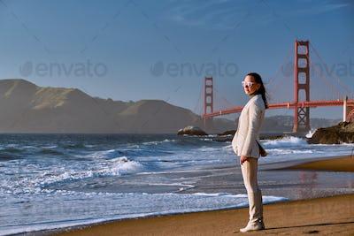 Woman on beach near Golden Gate Bridge