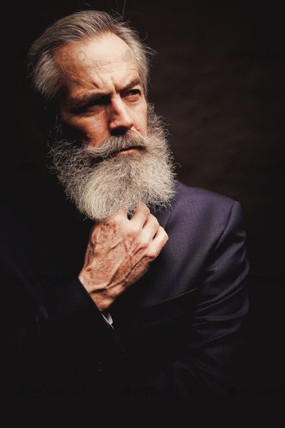 mature male model wearing suit with grey hairstyle and beard
