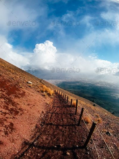 A mountain path bordered by red cliffs