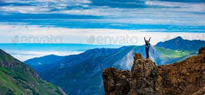 Young Woman Backpacker in Victory Pose with raised up arms on to