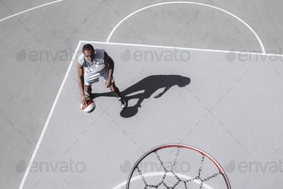 Picture of young confused african basketball player practicing