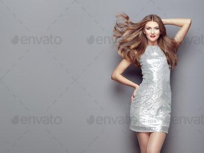Fashion portrait young woman in elegant silver dress
