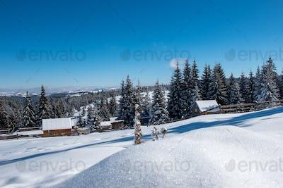 Idyllic winter wonderland mountain scenery with mountain chalet, lodge