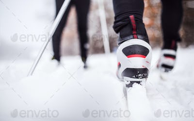 An unrecognizable couple cross-country skiing in winter.