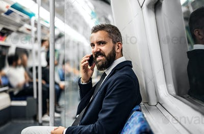 Hipster businessman with smartphone inside the subway in the city, travelling to work.