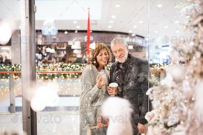 A happy senior couple doing Christmas shopping.