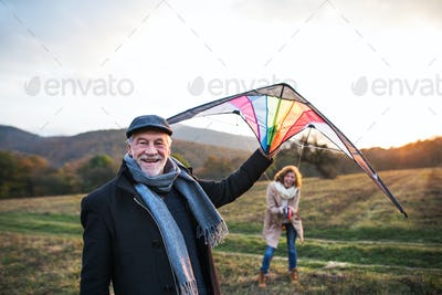 Carefree senior couple flying a kite in an autumn nature at sunset.