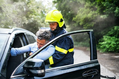 A firefighter getting an unconscious man out of the car after an accident.