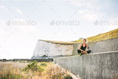 Young sporty woman runner with smartphone sitting on the beach outside.