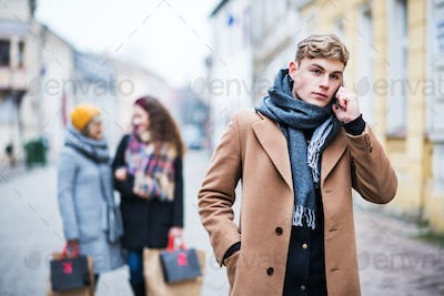 A portrait of teenage boy with smartphone on the street in winter.