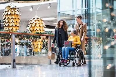 A grandmother in wheelchair and teenage grandchildren in shopping center at Christmas.