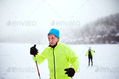A senior couple cross-country skiing in winter.