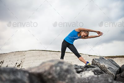 Young sporty woman runner with earphones standing on the rocks outside, stretching.