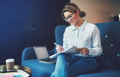 Smiling young businesswoman sitting on a sofa reading documents