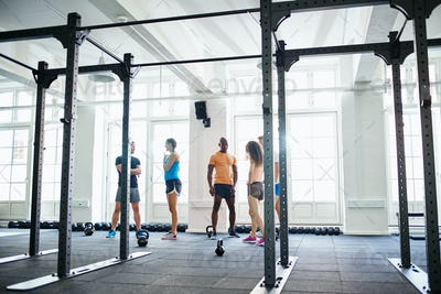 Diverse group of fit people talking together in a gym