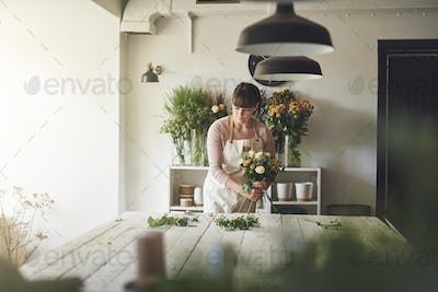 Young florist working in her flower ship making a bouquet