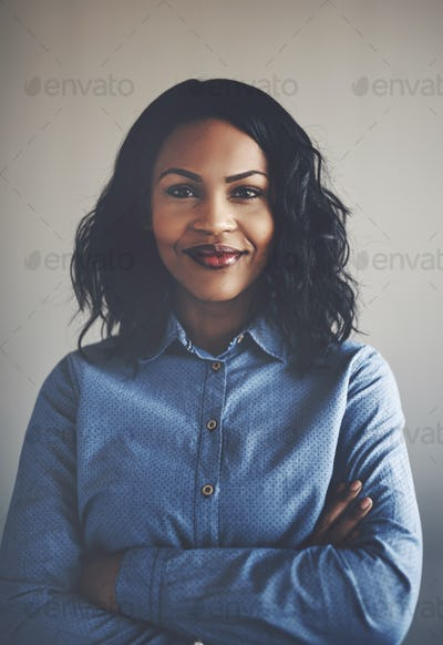 Confident young African businesswoman standing alone with her arms crossed