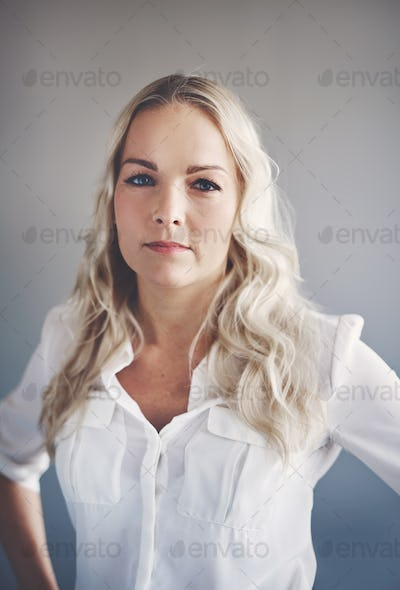 Focused young businesswoman standing alone in an office