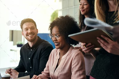 Smiling group of diverse businesspeople working together in an office