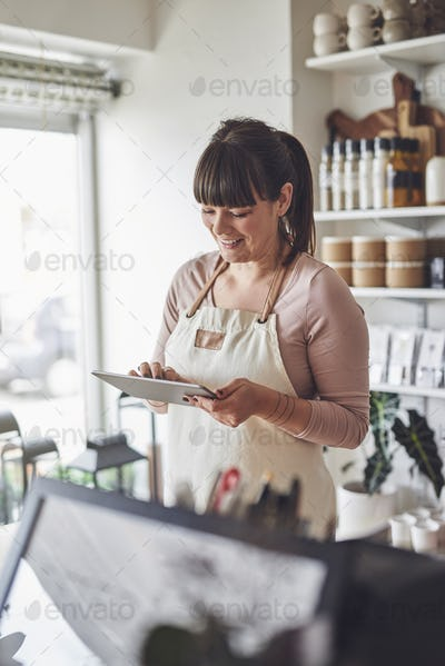 Smiling female florist using a tablet in her flower shop