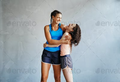 Two laughing girlfriends hugging each other after working out