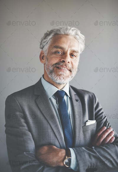 Smiling mature corporate executive standing with his arms crossed