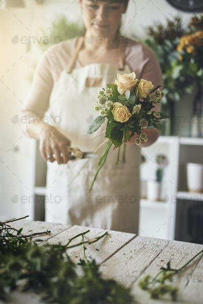 Young female florist working in her shop trimming flowers