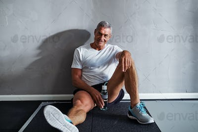 Smiling mature man taking a break after working out