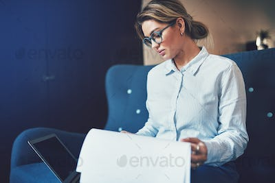Focused young businesswoman sitting on a sofa reading documents