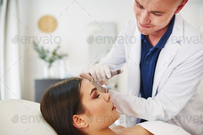 Doctor injecting botox into a female client's forehead
