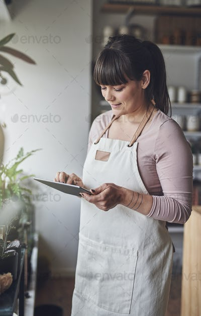 Smiling florist standing in her flower shop checking online orders