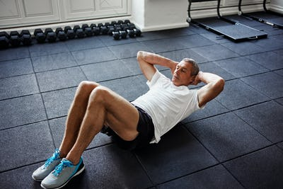 Mature man doing an ab workout in a gym