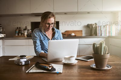 Female entrepreneur sitting in her kitchen working on a laptop