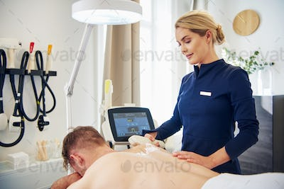 Clinic technician performing an electrolysis treatment on a client