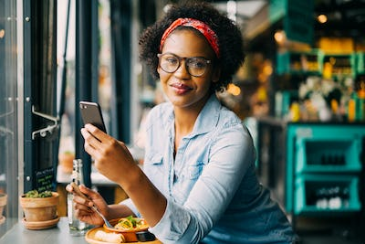 Young woman sending text messages over lunch in a cafe
