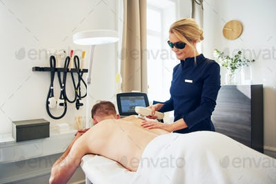 Beauty technician performing laser hair removal on a male client