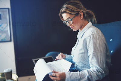 Young female entrepreneur reading paperwork on a sofa