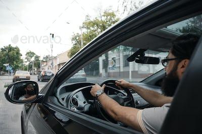 Modern casual bearded man driving a car